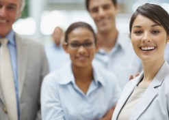 Portrait of young business executive smiling with colleagues